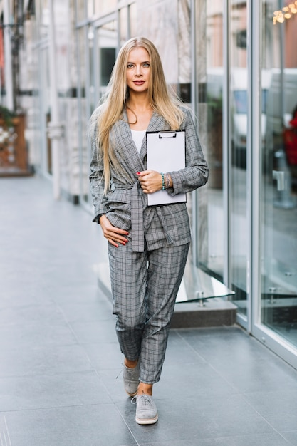 Stylish businesswoman with clipboard in city Free Photo