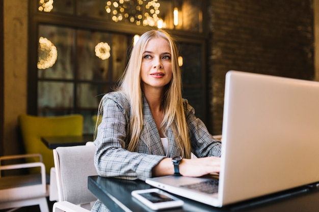 Stylish businesswoman with laptop at desk Free Photo