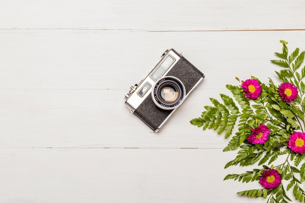 Stylish camera and pink flowers with green leaves Free Photo