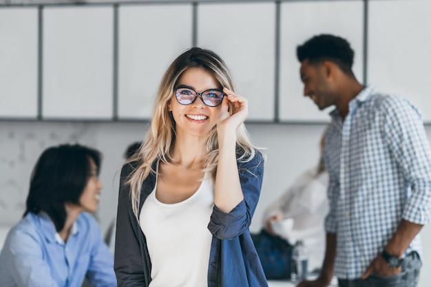 彼女の同僚が話している間、新しいオフィスでポーズをとっている黒いシャツを着たスタイリッシュな白人女性フリーランサー。友人との難しい試験の後に楽しんでいる眼鏡をかけた興奮した学生の屋内の肖像画。 無料写真
