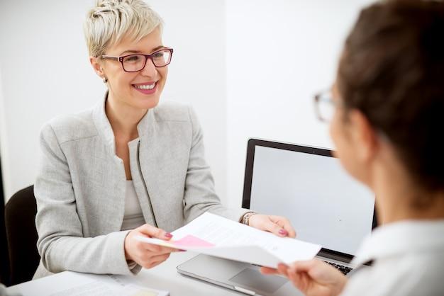 スタイリッシュな魅力的なショートヘアの中年幸せな女性は、オフィスで銀行員のためにすべての要求された書類を女性労働者から受け取ります。 Premium写真