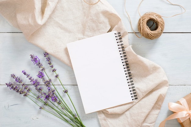 Stylish composition with lavender flowers, blank paper notepad, pastel beige blanket, twine, gift box on rustic blue wooden desk table Premium Photo