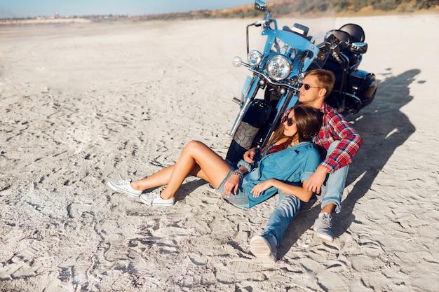 太陽が降り注ぐビーチで自転車に近いポーズの愛のスタイリッシュなカップル。 無料写真