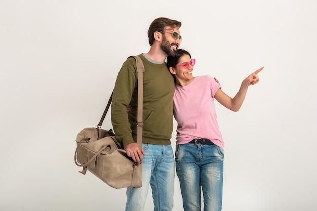 Изолированная стильная пара, симпатичная улыбающаяся женщина в розовой футболке и мужчина в толстовке с дорожной сумкой, одетый в джинсы, в темных очках, весело вместе, указывая пальцем Бесплатные Фотографии