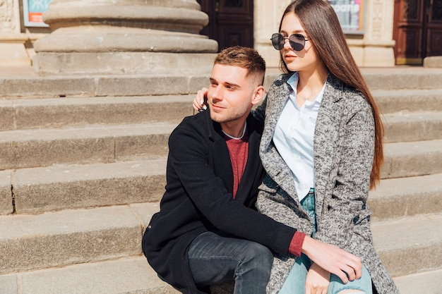 Stylish couple sitting on stairs and looking in one direction Free Photo