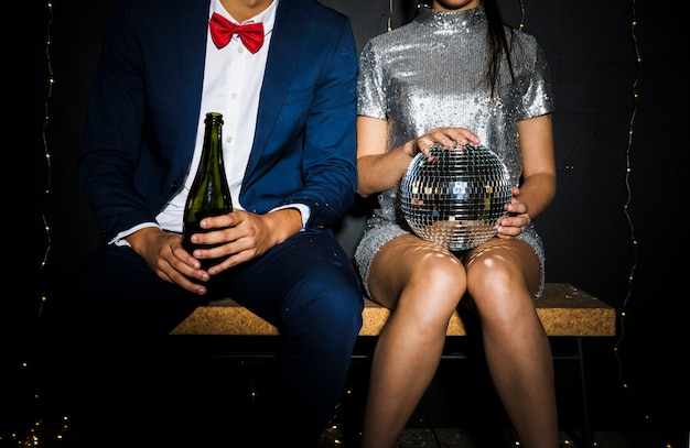Stylish couple with disco ball and bottle of champagne Free Photo