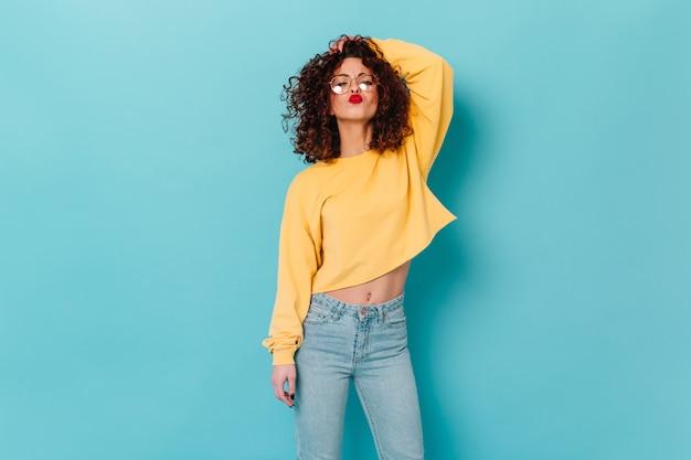빨간 립스틱으로 세련된 곱슬 여자가 머리를 만지고 키스를 불면. 안경에 푸른 공간에 노란색 스웨터 여자의 초상화. 무료 사진