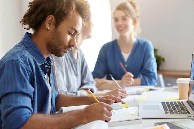 青いシャツを着たスタイリッシュな浅黒い肌の男性。勉強に忙しく、グループメイトの女性の近くに座って、ラップトップコンピューターで仕事をし、卒業証書を書きます。さまざまな人種の友好的な学生のグループ 無料写真