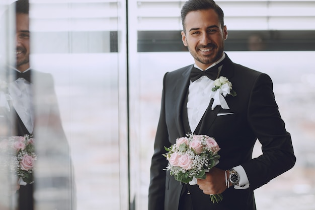The stylish and elegant bridegroom is in the hotel room with a bouquet of flowers Free Photo