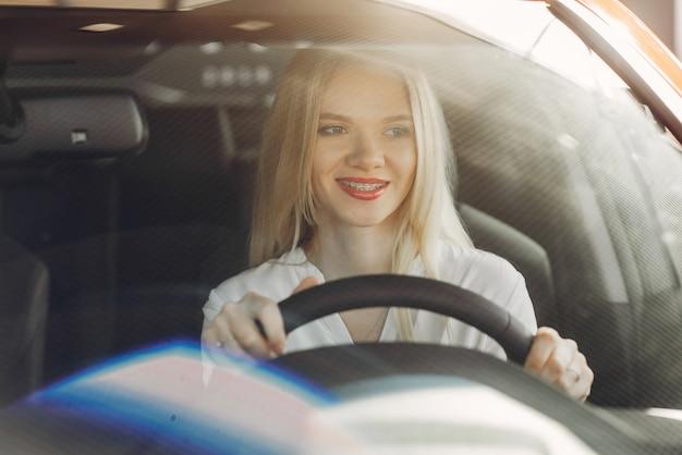 Stylish and elegant woman in a car salon Free Photo