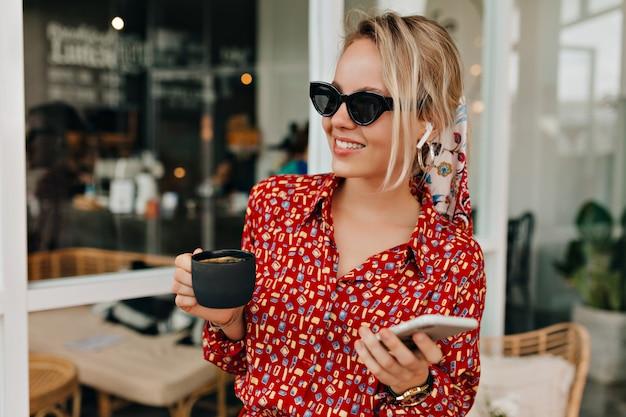 Стильная элегантная женщина в черных очках и ярком современном платье с чашкой кофе Бесплатные Фотографии