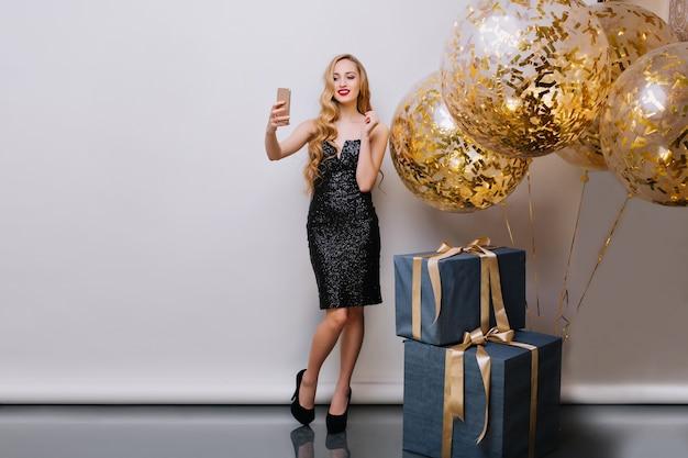 스마트 폰을 사용하여 생일 전에 사진을 만드는 붉은 입술로 세련된 국방과 소녀. 긴 금발 머리 선물과 미소로 풍선 근처 포즈와 멋진 젊은 여자의 실내 초상화. 무료 사진
