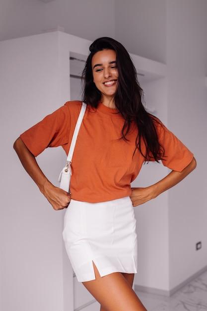 Стильная модная молодая кавказская женщина-блоггер дома в спальне в рубашке и юбке кирпичного цвета Бесплатные Фотографии