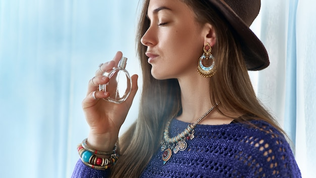 Stylish fashionable attractive brunette boho chic woman with closed eyes wearing jewelry and hat holds perfume bottle Premium Photo