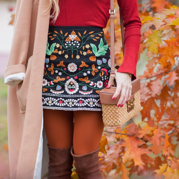 Stylish and fashionable girl in autumn foliage. autumn trend Premium Photo