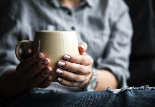 一杯のコーヒーとジーンズのマニキュアを持つスタイリッシュなファッショナブルな女の子。ファッション、ケア、美容 Premium写真