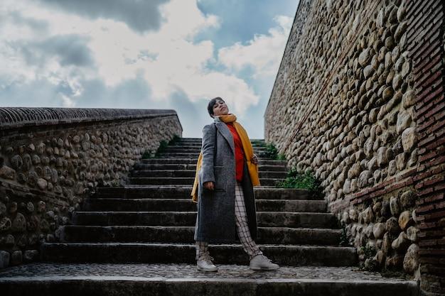 Una donna alla moda in un cappotto in posa davanti a una scala di pietra Foto Gratuite