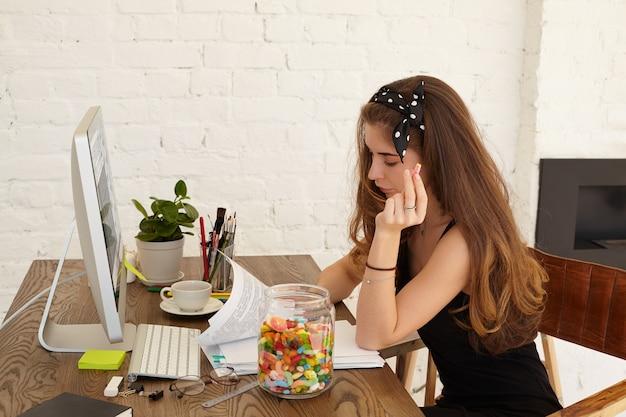 Стильная студентка школы экономики работает над дипломным проектом, сидит на своем рабочем месте дома с компьютером, бумажными листами и предметами интерьера на столе, ест сладости из стеклянной банки Бесплатные Фотографии
