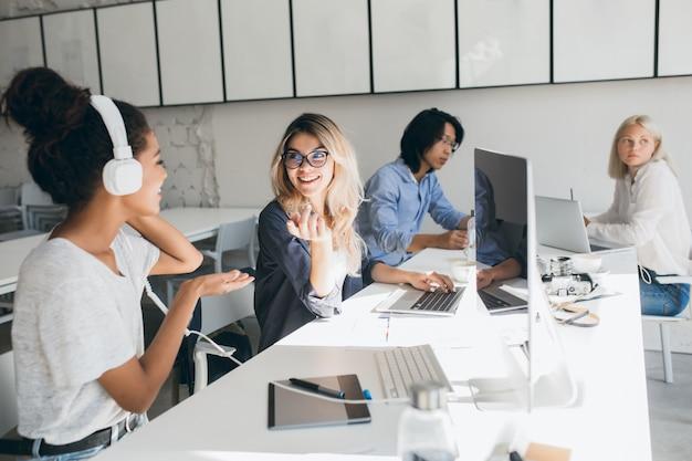 オフィスで時間を過ごしながら仕事について話しているスタイリッシュな女性のウェブプログラマー。コンピューターを使用してヘッドフォンとアジアの労働者のアフリカの女性の屋内の肖像画。 無料写真