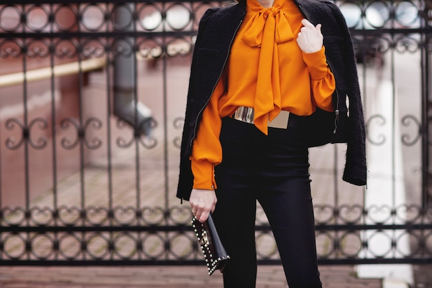 Stylish girl in a black suit and orange blouse stands near the fence Premium Photo