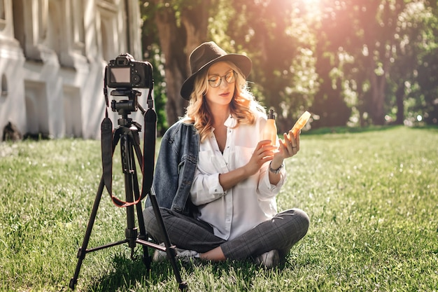 Stylish girl blogger sitting on the street on the grass and shoots vlog on camera. Premium Photo