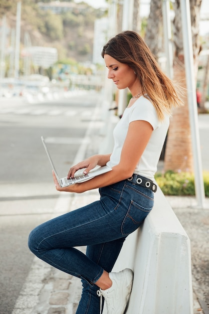 Stylish girl holding a laptop outdoor Free Photo