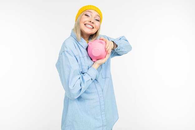 Стильная девушка в синей рубашке с банком для сохранения финансов на белом фоне с копией пространства Premium Фотографии