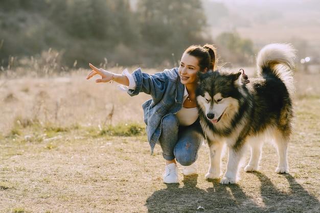 Стильная девушка в солнечном поле с собакой Бесплатные Фотографии