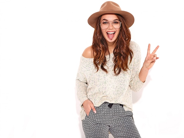 Stylish girl model in casual summer clothes in brown hat with natural makeup in glasses isolated., showing her tongue and peace sign Free Photo