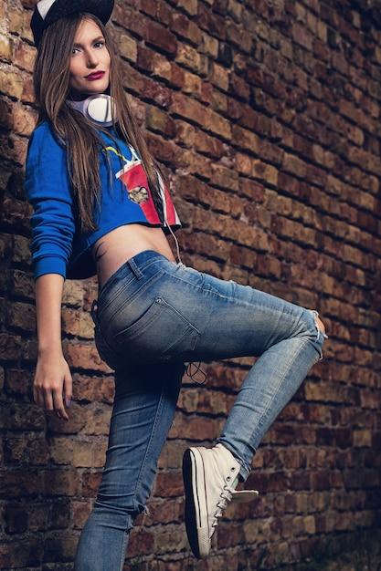 Stylish girl posing near a brick wall Free Photo