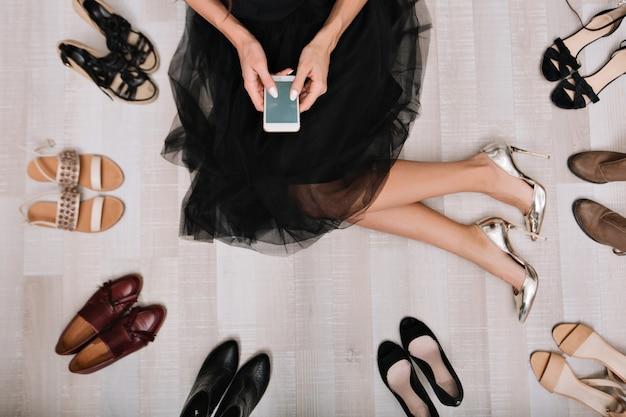 Elegante ragazza seduta sul pavimento in uno spogliatoio con lo smartphone in mano, scrive il messaggio, circondato da una varietà di scarpe. è vestita con una gonna nera, ai piedi scarpe di lusso d'argento. Foto Gratuite
