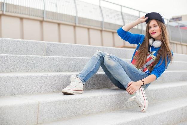 Стильная девушка сидит на ступеньках Бесплатные Фотографии