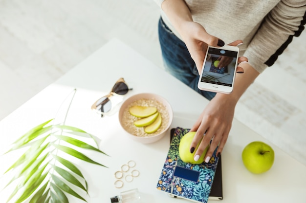 Stylish girl taking pictures with apple, notebook on whie table. Free Photo