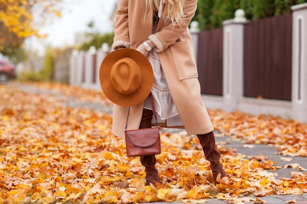 Stylish girl walks in autumn park in a beige coat and hat Premium Photo