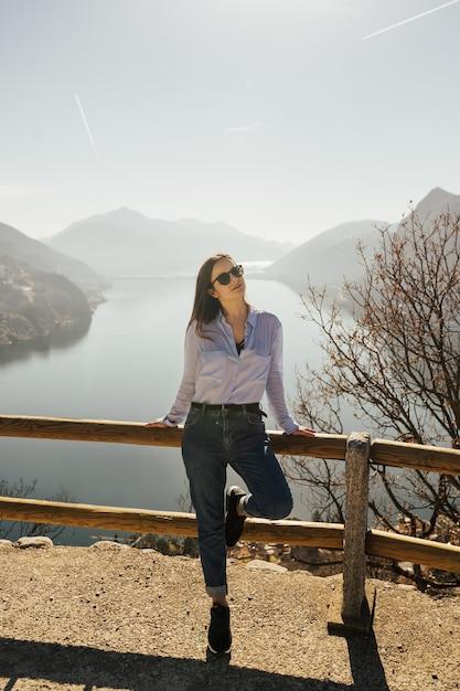 スイスのルガーノ湖を背景に丘の上にメガネと青いシャツを着たスタイリッシュな女の子。 Premium写真