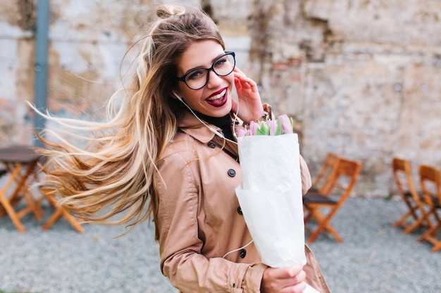 Stylish girl with pretty hairstyle wearing glasses fools around and laughs carrying tulip bouquet. adorable young woman in beige jacket with blonde streaming hair smiling on the blur background. Free Photo