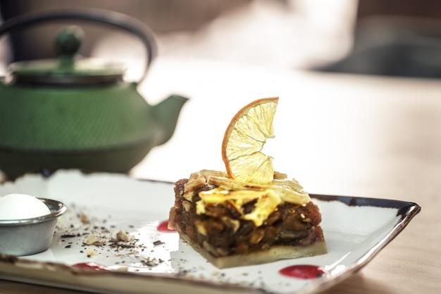 お茶と甘いデザートのスタイリッシュなグリーンケトル。レモンとコールドアイスクリームをキャラメリゼしたアップルパイ 無料写真