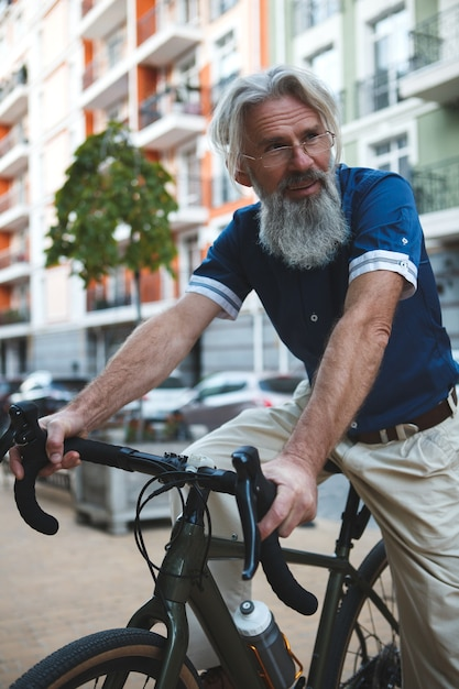 도시의 거리에서 자전거를 타는 세련된 회색 머리 수염 남자 프리미엄 사진
