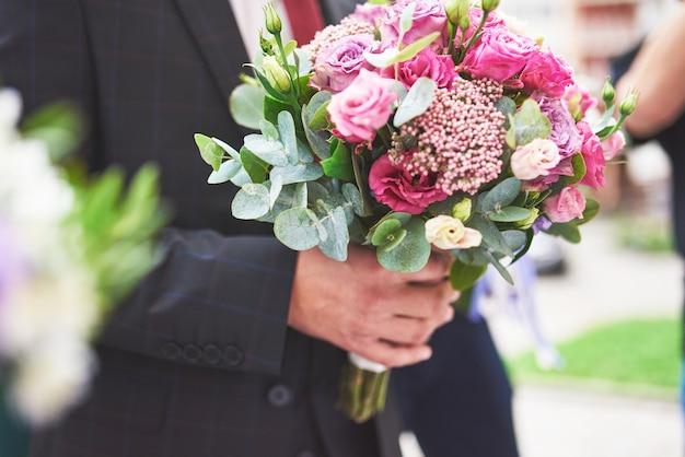 Sposo alla moda che tiene un bouquet da sposa rosa tenero. Foto Gratuite