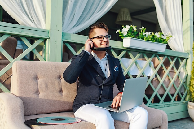 Stylish guy in glasses and formal suit on sofa with laptop and headphones Premium Photo