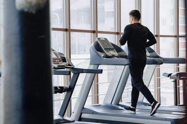 Стильный парень в тренажерном зале занимается на беговой дорожке. здоровый образ жизни. Бесплатные Фотографии