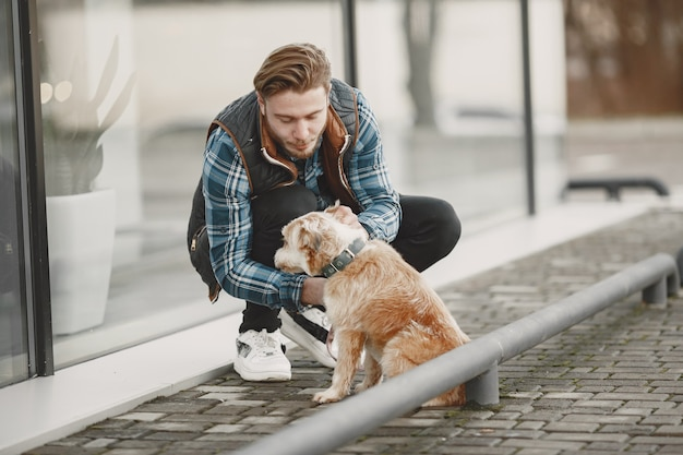 Stylish guy playing with a dog. man in autumn city. Free Photo