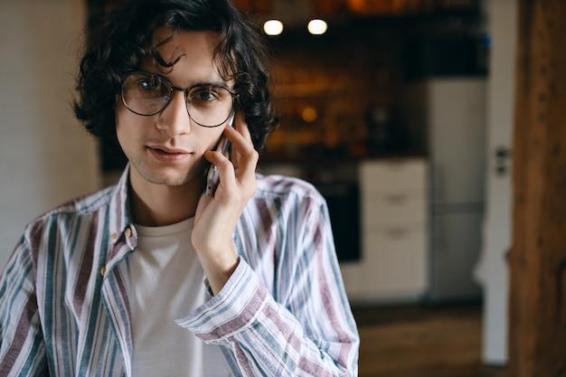 モバイルを使用して電話で会話している居心地の良いキッチンのインテリアに対してポーズをとる巻き毛のスタイリッシュな男 無料写真