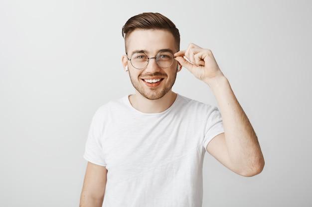 Стильный красивый мужчина в очках слушает музыку в беспроводных наушниках Бесплатные Фотографии