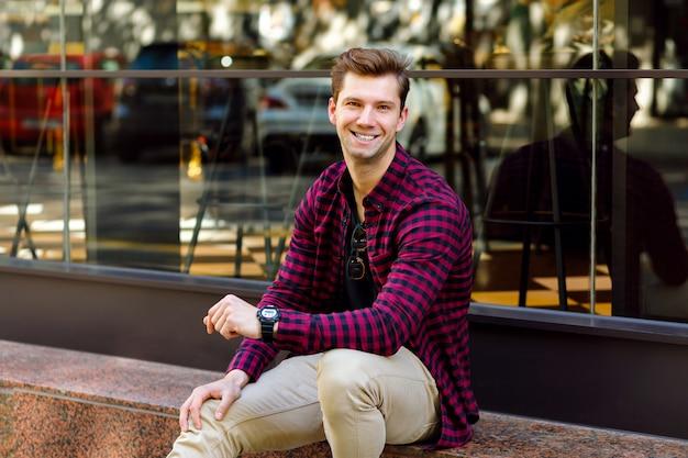 Стильный красивый молодой бизнесмен сидит на улице, удивительная улыбка, каштановые волосы и глаза, в клетчатой рубашке и бежевых брюках, солнцезащитных очках и часах, позирует возле ресторана. Бесплатные Фотографии