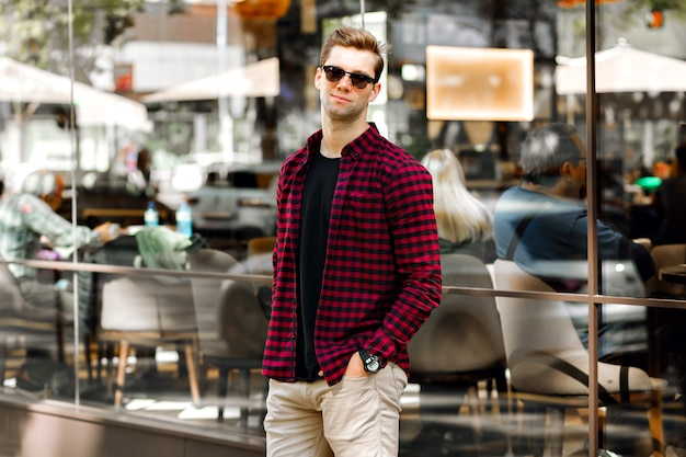 Stylish handsome young businessman sitting on the street, amazing smile, brown hairs and eyes, wearing hipster plaid shirt and beige trousers, sunglasses and watches, posing near restaurant. Free Photo