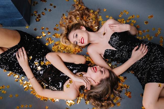 金色のティンセルに横たわる豪華な黒のドレスを着た2人の魅力的な若い女性の上からのスタイリッシュなハッピーパーティーの画像。楽しんで、笑って、笑って、真のポジティブな感情を表現する。 無料写真