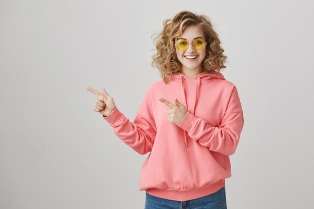 Elegante ragazza adolescente felice in occhiali da sole che mostrano il modo, promuovere la pubblicità Foto Gratuite