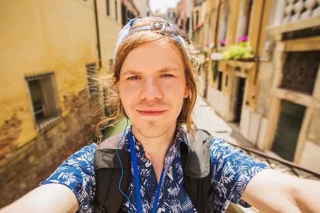 ヴェネツィアの運河の背景にselfieを取ってキャップでスタイリッシュな幸せな若い男。イタリアの幸せな観光客。ヨーロッパへ旅行します。クローズアップの肖像画。電話で自分撮りを取る。ヴェネツィアの観光。ベネチアン運河 Premium写真