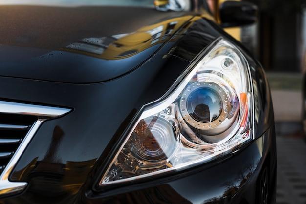 Elegante faro di auto scura parcheggiata in strada Foto Gratuite